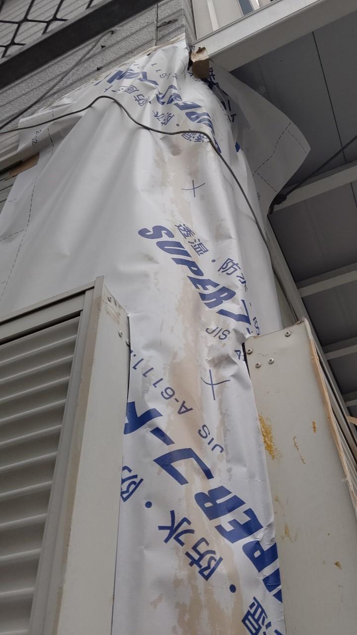 破損した外壁サイデイングに防水シートを張った写真